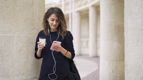 Young businesswoman drinking coffee and listening to music outside. Young woman wearing a black business suit is drinking a coffee to go and listening to the stock video footage