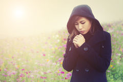 Young woman wearing black cloth very cold in flower garden Royalty Free Stock Images
