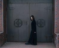Young woman wearing black clothes posing near gates Stock Photos