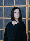 Young woman wearing black clothes posing near gates Stock Images