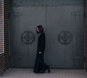 Young woman wearing black clothes posing near gates Royalty Free Stock Image