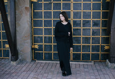 Young woman wearing black clothes posing near gates Royalty Free Stock Photos
