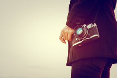 Young woman wearing black coat standing carry retro camera. Woman wearing black coat standing carry retro camera Stock Image