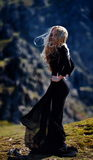 Young woman wearing black dress outdoor on rocks Royalty Free Stock Photography