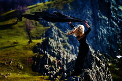 Young woman wearing black dress outdoor on rocks Stock Photos