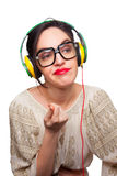 Young Woman wearing Black Large Framed Glasses Listening to Head. Phones and making silly faces Stock Photography