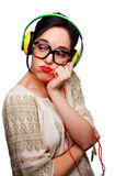 Young Woman wearing Black Large Framed Glasses Listening to Head. Phones and making silly faces Royalty Free Stock Images
