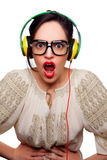 Young Woman wearing Black Large Framed Glasses Listening to Head. Phones and making silly faces Stock Photo
