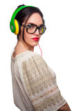 Young Woman wearing Black Large Framed Glasses Listening to Head. Phones and making silly faces Royalty Free Stock Photos