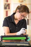 Young woman wearing black shirt performing toner change and printer maintenance, concentrated facial expressions Stock Photo