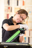 Young woman wearing black shirt performing toner change and printer maintenance, positive attitude smiling Royalty Free Stock Images
