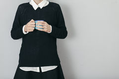 Young woman wearing black sweater and skirt holding a cup of cof Stock Photo