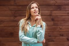 Young woman in blouse standing isolated on wall looking up pensive royalty free stock photos