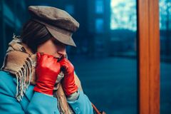 Young woman wearing blue coat, cap and gloves. Spring female clothes and accessories. Fashion royalty free stock photography