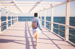 Young woman wearing blue coat walking near the sea. Back view royalty free stock photos