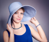 Young woman wearing blue dress and blue big hat Stock Images