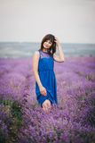 Young woman wearing blue dress standing in a lavender field Stock Photos