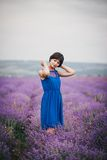 Young woman wearing blue dress standing in a lavender field Stock Photo