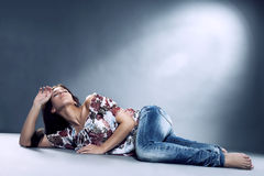 Young woman wearing blue jeans lying on the floor Royalty Free Stock Photos