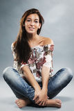 Young woman wearing blue jeans sitting on the floo Stock Photo