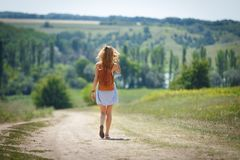 Young woman with a leather backpack on a summer rural road. Young woman wearing blue summer dress with a brown foxy leather backpack walking on rural road with a Stock Photography