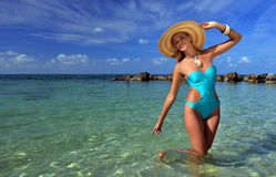 Young woman wearing blue swimsuit and straw hat Royalty Free Stock Image