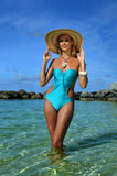 Young woman wearing blue swimsuit and straw hat Stock Photography