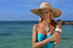 Young woman wearing blue swimsuit and straw hat. Standing in shallow tropical water Stock Photo