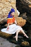 Young woman wearing boho chic scarf on a head and handmade feathers necklace and earrings. Outdoor horizontal photo with space for text against stone stock photography