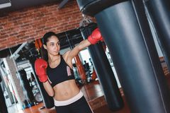 Young woman in boxing gloves in gym standing kicking punching bag concentrated royalty free stock photography