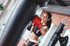 Young woman in boxing gloves in gym standing kicking punching bag breathing royalty free stock image