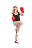 Young woman wearing boxing gloves and raising foot and hand Stock Photography