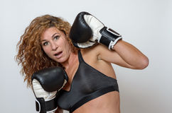 Young woman wearing boxing gloves royalty free stock photography