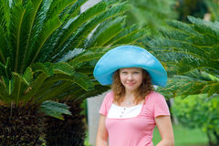 Young woman wearing bright blue hat in Palm's garden Royalty Free Stock Photography