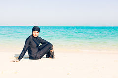 Young Woman Wearing Burkini Sitting By The Beach Royalty Free Stock Images