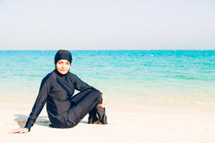 Young Woman Wearing Burkini Sitting By The Beach Stock Photos