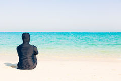 Young Woman Wearing Burkini Sitting By The Beach Stock Images