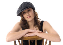 Young woman wearing a cap. Woung woman sitting on a chair royalty free stock photos