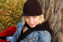 Young woman wearing cap and scarf. Beautiful young woman outdoors in Autumn wearing a cap and scarf Stock Photography