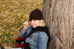 Young woman wearing cap and scarf. Beautiful young woman outdoors in Autumn wearing a cap and scarf Royalty Free Stock Photography