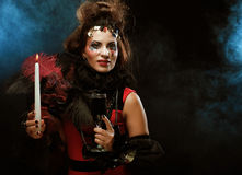 Young woman wearing carnival costume holding a candle. Stock Image