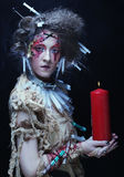 Young woman wearing carnival costume holding a candle. royalty free stock photo