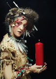 Young woman wearing carnival costume holding a candle. royalty free stock photography
