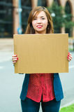 Young woman wearing casual clothes standing outdoors holding up cardboard poster, protesting concept Royalty Free Stock Image