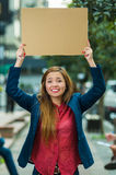 Young woman wearing casual clothes standing outdoors holding up cardboard poster, protesting concept Royalty Free Stock Images