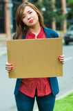 Young woman wearing casual clothes standing outdoors holding up cardboard poster, protesting concept Royalty Free Stock Photography