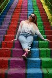 Young woman wearing casual clothes and sunglasses sits on rainbow painted stairs