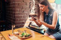 Young woman wearing casual clothes taking picture of her healthy lunch sitting on windowsill in trendy cafe.  Stock Images