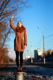 Young woman wearing coat stands on a stand, cold winter day, han Royalty Free Stock Photos
