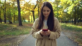 Young woman wearing a coat or trench using smartphone walking in autumn park stock footage